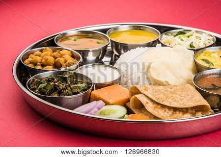 Group of Indian Food or Indian Thali, south indian thali, south indian compleat meal, south indian complete lunch, over red background