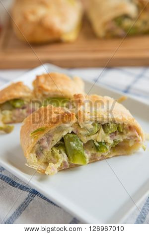 Home made vegetable strudel with asparagus, cheese and ham