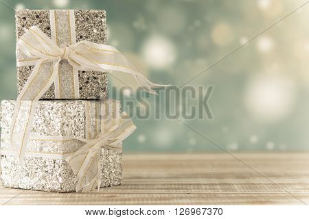 Gift boxes placed on a wooden table against the background bokeh. For Christmas New Year and Valentine's Day concept.