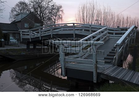 Typical dutch wooden bridge, in the countryside from the Netherlands at sunset