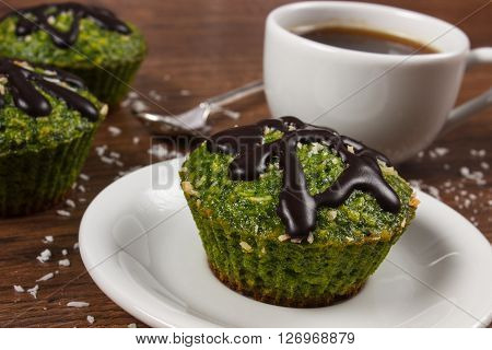 Homemade fresh muffins baked with wholemeal flour with spinach desiccated coconut and chocolate glaze cup of coffee delicious healthy dessert or snack