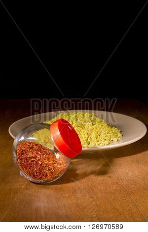 Yellow rice with saffron in a glass container on a wooden table