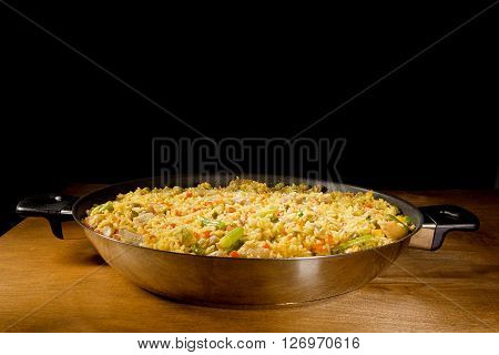 Overhead shot of a pot of chicken paella a traditional Valencian (Spanish) rice dish made of rice chicken peas and capsicum.