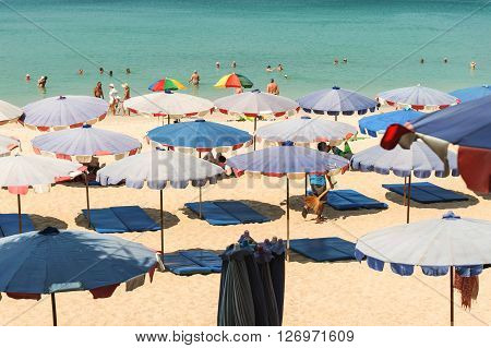 PhuketThailand - March 01 2016: Parasol and some people relax on the white sand beach and blue sea with blue sky background