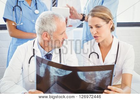 Two doctors examining an x-ray report in hospital