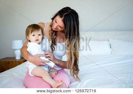 smiling brunette woman is holding a cute baby on a bed