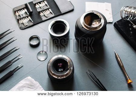 Precision optical dslr lens service, adjustment and alignment. Camera lens repair set in photo engineer workspace. Maintenance support of photographic 50 1.4 photo camera lens.