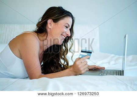 smiling woman lying down holding her laptop and credit card