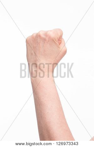 Old woman's fist up in white isolated background. Hand with clenched fist in studio demostrating power and protection.