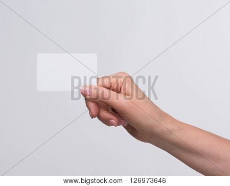 Old woman holding credit card over white background in her right hand. Beautiful hand of woman represented over white background.