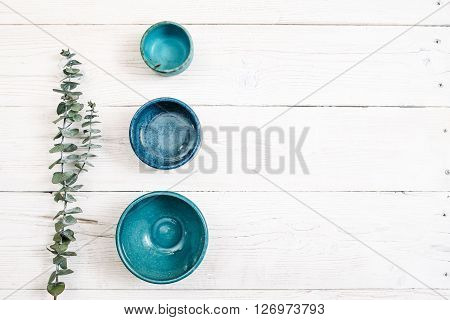 Three turquoise clay empty plates and evergreen branch on a white wooden background. Top view on set of trendy empty plates for a restaurant. Organic food, beautiful life, pottery, decoration concept
