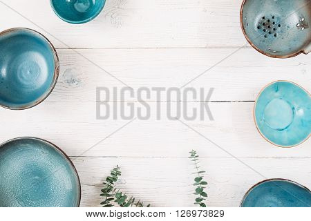 Many turquoise clay empty plates and free space in center on a white wooden background. Top view on set of trendy handmade empty plates. Organic food, healthy life, pottery, decoration concept