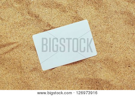 Top view of blank business card in hot beach sand blank copy space for summer holiday vacation travel agency message.
