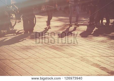 Young people on the street blur defocussed image of young pedestrians walking in late afternoon retro toned