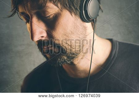 Unshaven adult DJ man listening to music on headphones enjoy favorite song with his eyes closed.
