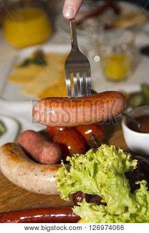 Sausage impaled on a fork on the background plate with fresh herbs and sauces