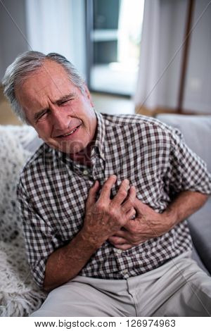 Senior man suffering from heart attack at home
