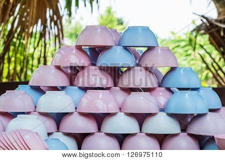 Piles of colorful plastic crockery bowl on wooden desk