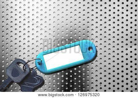 Keys with blank key fob on aluminum texture background