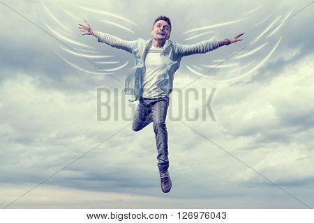 Young man with drawn wings flying in sky background