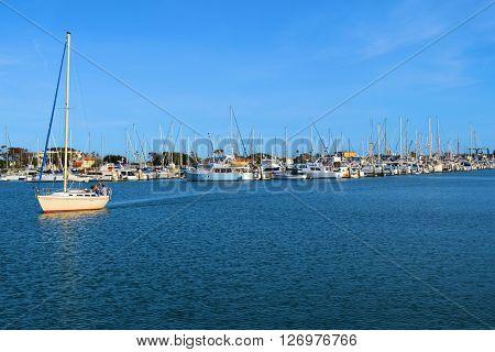April 20, 2016 in Ventura, CA:  Sail boat heading out to sea taken at Ventura Harbor in Ventura, CA