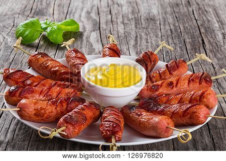 Grilled sausages on skewers on a white dish with mustard in a gravy boat on an old rustic table studio lights top view close-up