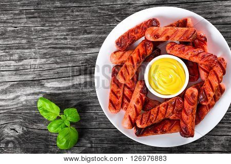 Grilled sausages decorated with basil leaves on a white dish on an old rustic table mustard in a gravy boat studio lights top view