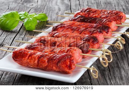 Grilled sausages on skewers on a white dish with mustard in a gravy boat on an old rustic table studio lights close-up full focus
