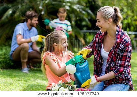 Happy mother and daughter enjoying while watering flowers in yard