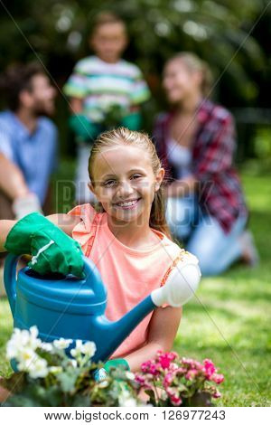 Smiling girl with watering can sitting on grass in yard