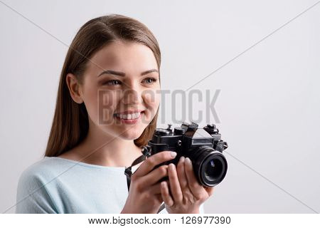 Real photographer.  Cheerful content charming girl smiling and holding photo camera while going to make photos