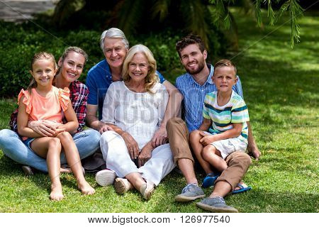 Portrait of multi generation family relaxing on grass at yard