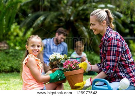 Mother giving flower pot to smiling daughter while sitting in yard