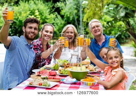 Happy family having breakfast at table in yard