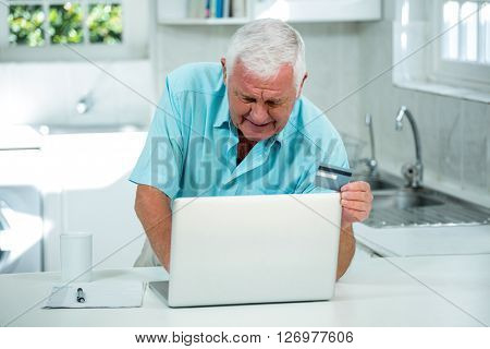 Senior man using laptop for online shopping on kitchen counter at home