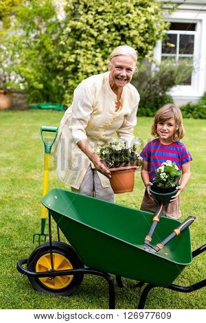Smiling grandmother with boy holding flower pots on grass at yard
