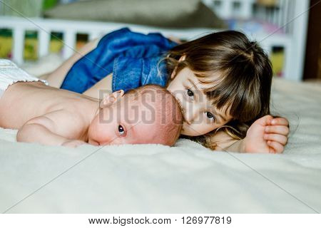 Cute little girl is playing with her younger brother at home lying on the bed