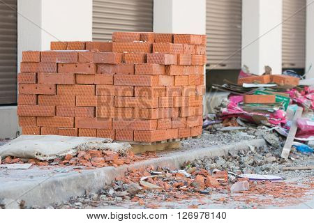 New bricks are stacked on a pallet stand at the trade pavilions around construction debris
