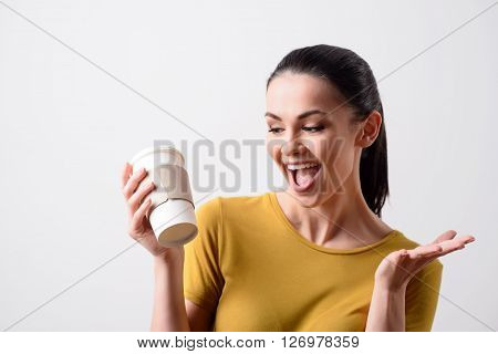Restore your energy. Positive smiling content joyful woman drinking coffee and expressing gladness while standing isolated on grey background