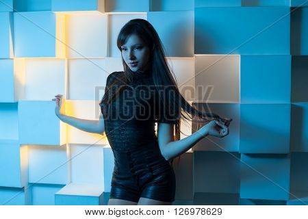 Young brunette lady in black t-shirt and shorts posing on abstract square background. Blue light