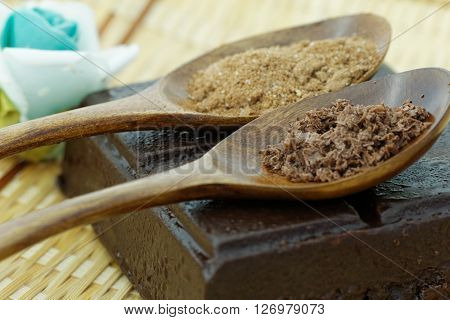 Dark chocolate powder and cocoa powder in wooden spoon with dark chocolate bar.
