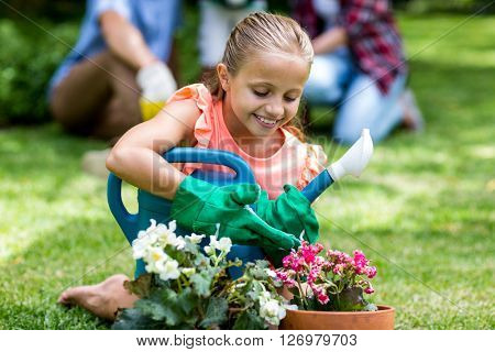 Smiling girl holding watering can by flower pots at yard