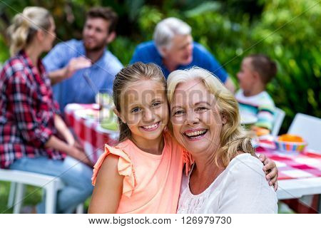 Portrait of smiling granny carrying girl during breakfast at yard