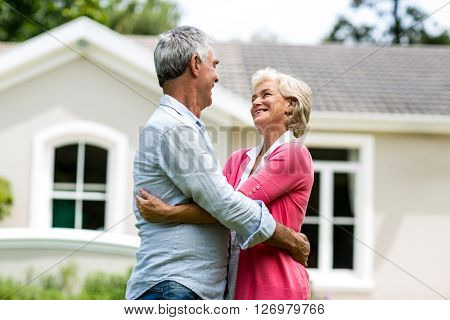 Smiling senior couple with arms around against house at yard