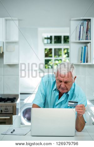 Senior man doing online shopping by using laptop in kitchen at home
