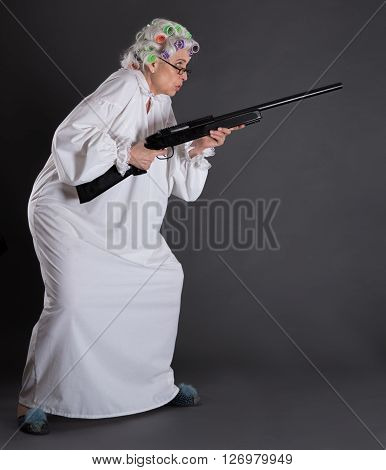 Serious grandmother posing with rifle in studio imagining that she is protecting her house from robberies. Elderly in defence.