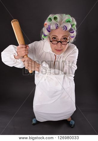 Top view of crazy furious grandmother holding criket bat and looking at camera. Beautiful lady with rollers on in studio.