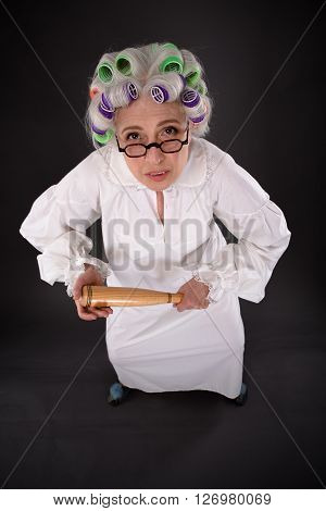 Top view of crazy furious grandmother in glasses looking at camera and holding criket bat over dark grey background.