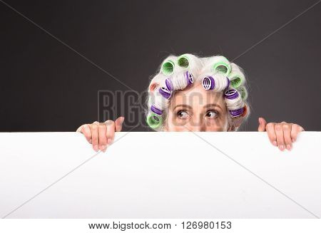 Grandmother hiding behind white poster and looking away. Beautiful lady with rollers on in studio. Studio shot. Copyspace.