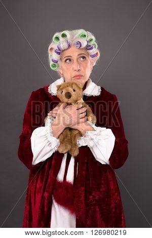 Pretty grandmother posing with teddy bear over grey background having nostalgia about old times in her childhood.